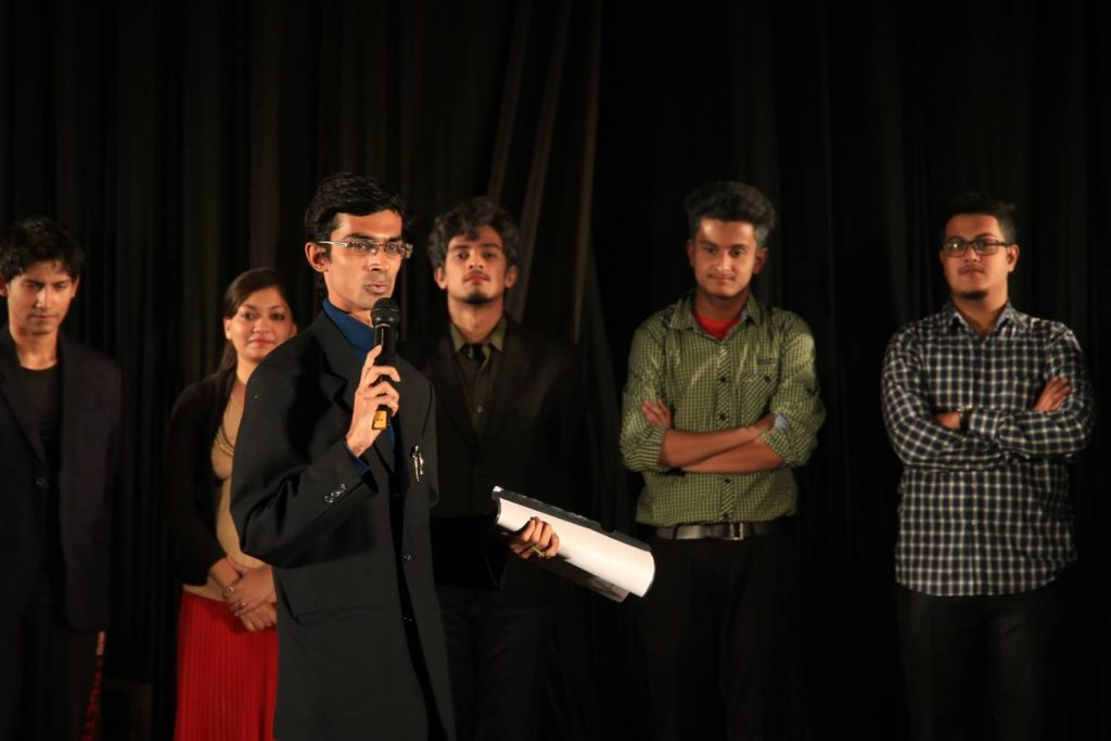 Director, Dr. Nilanko Mallik, addresses the audience after the show, with actors looking on.
