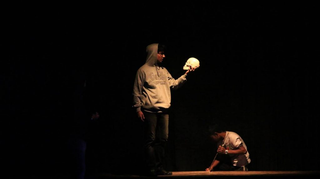 Ophelia's funeral scene, with a Gravedigger and Hamlet holding a skull.